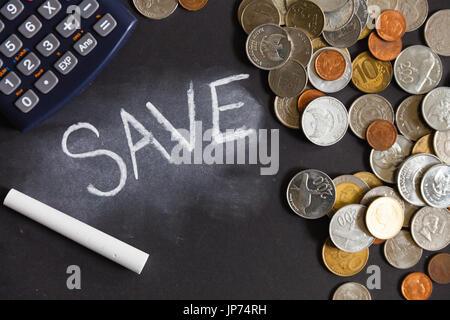 : Sparen Rechner und Münzen aus verschiedenen Ländern liegen auf einem Tisch auf einem schwarzen Hintergrund mit - Stockfoto