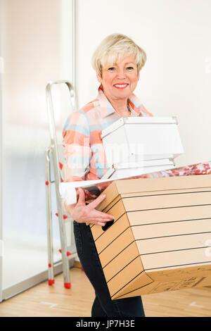 Ältere Frau bewegen Häuser - Stockfoto