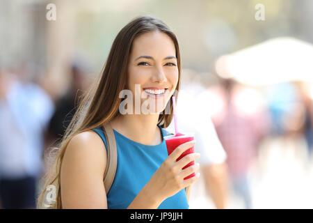 Glückliche Frau hält ein Matsch und schauen Sie auf der Straße - Stockfoto