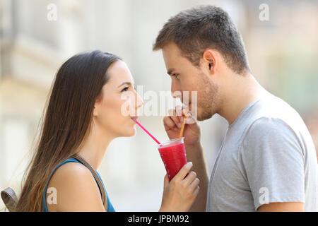 Seite Ansicht Porträt ein glückliches Paar, schlürfen einen Matsch zusammen draußen auf der Straße - Stockfoto