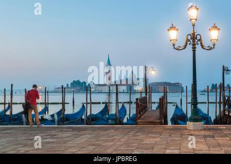 Ein einsamer Mann wartet vor der Gondeln, die entlang der Riva Degli Schiavoni angedockt. im Hintergrund die Insel San Giorgio Maggiore, Venedig, Italien