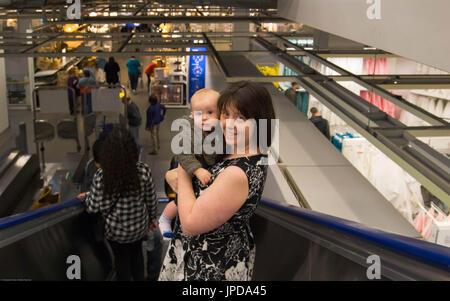 Eine Rolltreppe mit Baby hinunter. Stockfoto