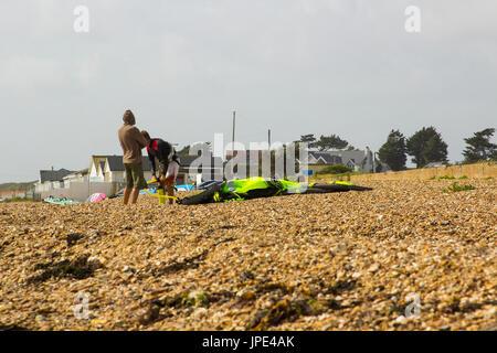 Ein paar junge Männer Kampf gegen eine steife Brise, bereiten Sie ihre Para-Gleiter für einen Nachmittag Sport am - Stockfoto