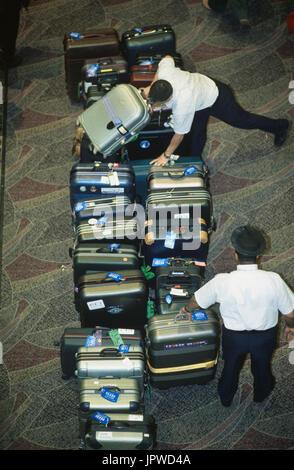 Porter mit Doppellinie Koffer aus Gepäckausgabe Karussell-Kollektion von Passagieren in der Ankunftshalle erwartet - Stockfoto
