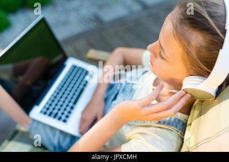 Nahaufnahme von Recht jugendlich Mädchen Kopfhörer anhören von Musik mit einem Laptop und sitzen draußen auf der - Stockfoto