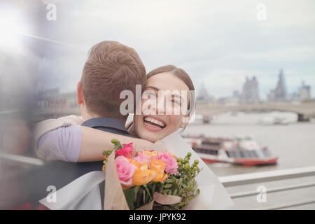 Glücklich, dankbar Frau blumeblumenstrauß empfangen, umarmt Freund an städtischen Uferpromenade - Stockfoto
