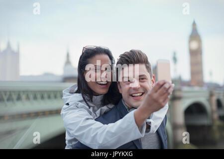 Verspielt, zärtlich paar Touristen nehmen Selfie mit Kamera-Handy vor der Westminster Bridge, London, UK - Stockfoto