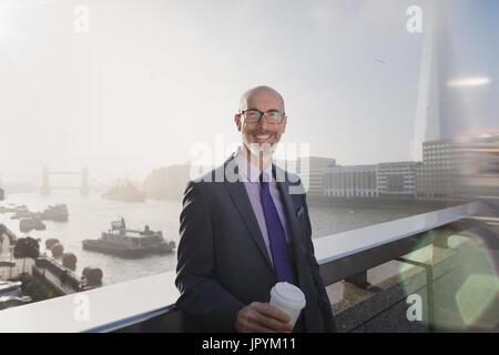 Porträt lächelnd, zuversichtlich Geschäftsmann Kaffeetrinken auf sonnigen städtische Brücke über die Themse, London, - Stockfoto