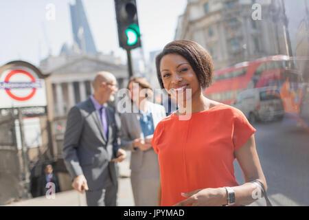 Porträt lächelnd Geschäftsfrau in der sonnigen Stadt Street, London, UK - Stockfoto