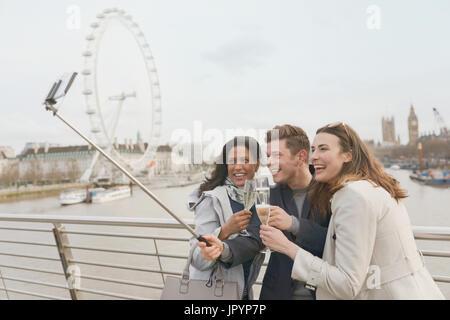 Lächelnd Freund Touristen feiern, toasten, Champagner und nehmen Selfie mit Selfie Stock in der Nähe von Millennium - Stockfoto