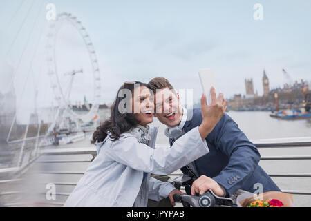 Lächelnde paar Touristen nehmen Selfie mit Kamera-Handy auf Brücke in der Nähe von Millennium Wheel, London, UK - Stockfoto