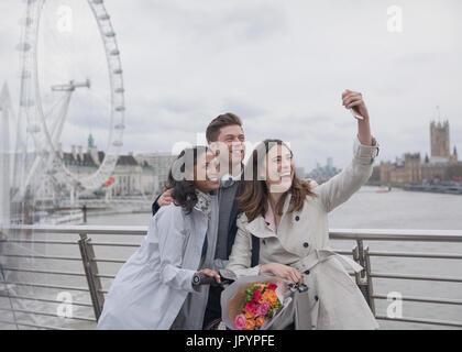 Lächelnd, glücklich Freunde nehmen Selfie mit Selfie Stick auf Brücke in der Nähe von Millennium Wheel, London, - Stockfoto