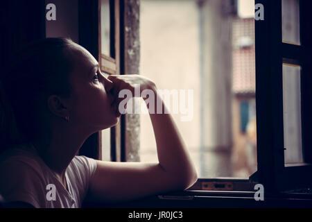 Nachdenklich nachdenklich junge Frau in Gedanken träumen und Suchen in geöffneten Fenster im traditionellen Stil - Stockfoto