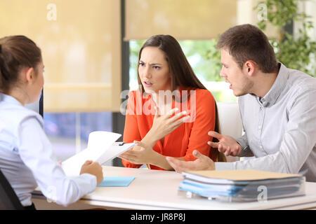 Wütend paar streiten, sagen ihre Probleme in einem Desktop eine Eheberatung oder im Büro sitzen - Stockfoto