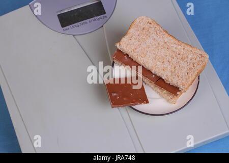 Dunkles Brot Schokolade Sandwich auf eine Personenwaage im Querformat mit Textfreiraum - Stockfoto