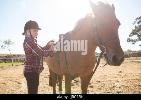 Mädchen einstellen Sattel auf dem Pferd in der Ranch an einem sonnigen Tag - Stockfoto