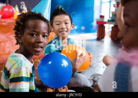 Portrait von spielenden Kindern mit Ballon in Rood während der Partei - Stockfoto