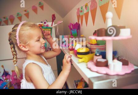 Glückliches Mädchen an ihrem Spielzeug an Bord. Horizontale drinnen geschossen. - Stockfoto