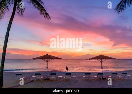 Ein paar Bummeln am Seven Mile Beach in der Karibik bei Sonnenuntergang, Grand Cayman, Cayman Islands - Stockfoto