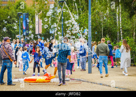 Straße Entertainer Hereinholen Tipps unterhalten Kinder durch Einblasen große bunte Luftblasen, Bankside, Böschung, - Stockfoto