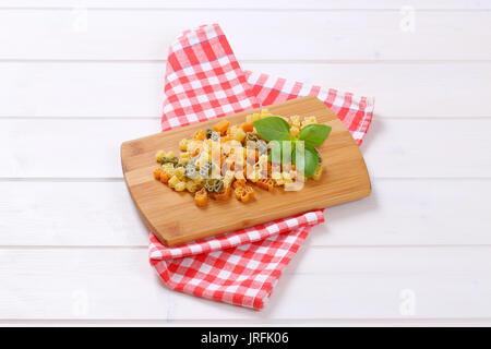 Stapel der Raw-farbigen Nudeln auf Holz Schneidebrett - Stockfoto