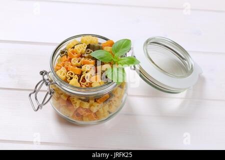 Jar von rohem Holz farbige Pasta auf weißem Hintergrund - Stockfoto