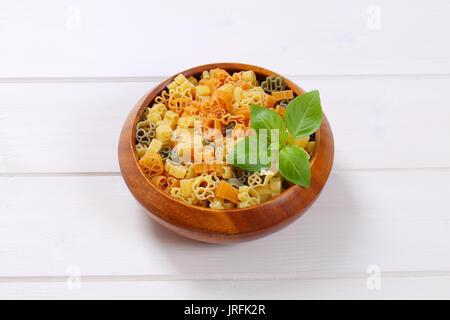 Schale der rohen farbige Pasta auf weißem Holz- Hintergrund - Stockfoto