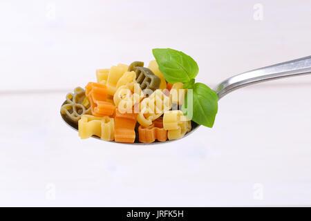 Löffel, raw-farbigen Nudeln auf weißem Holz- Hintergrund - Stockfoto