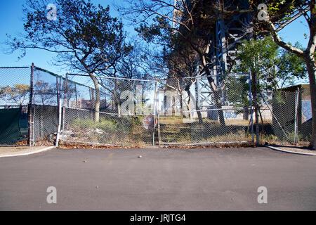 Zerschlagene, geschlossener Zaun Tor unter der Williamsburg Bridge in Manhattan, New York, NY, USA. - Stockfoto