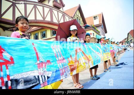 Qingdao, China Shandong Provinz. 5. August 2017. Kinder präsentieren eine 100-Meter-Schriftrolle, die sie in Qingdao, - Stockfoto