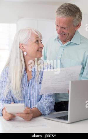 Älteres Paar, die Überprüfung der nationalen Finanzen lächelnd - Stockfoto