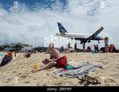 Eine JetBlue Airbus A320 landet auf Princess Juliana International Airport als Touristen nehmen Sie Fotos von Maho - Stockfoto