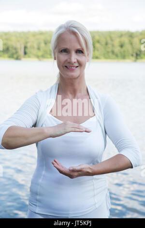 Frau tun Qi Gong auf einem Bootssteg - Stockfoto