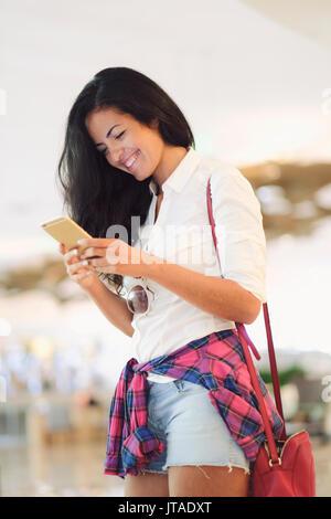 Junge brasilianische Frau mit Ihrem Mobiltelefon im Zentrum von Rio de Janeiro, Brasilien - Stockfoto