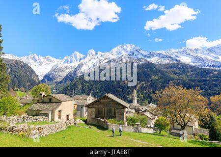 Blick auf soglio zwischen Wiesen und schneebedeckten Gipfeln im Frühjahr, Maloja, Bergell, Engadin, Kanton Graubünden, - Stockfoto