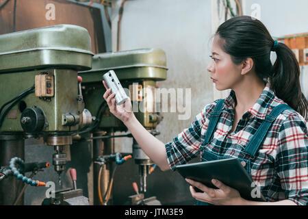 Schöne Fräsbearbeitung Mitarbeiter Mädchen, dass mobile digital Tablet Stand vor der Bohrmaschine und Holding Komponenten zu tun.