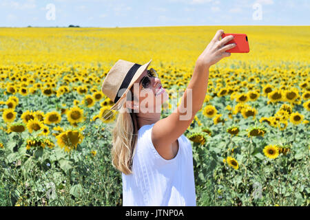 Fröhliches Mädchen unter selfie in einem blühenden Sonnenblumen Feld - Stockfoto