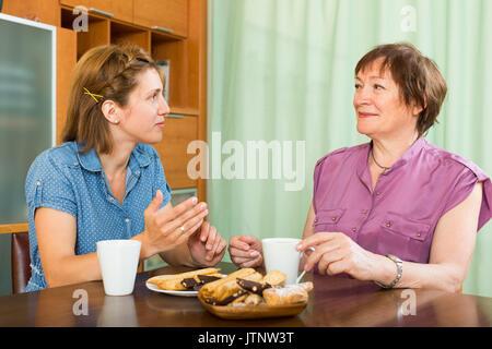 Ältere Frau und Tochter am Tisch sitzen und Tee trinken. - Stockfoto