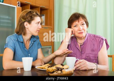 Alter Rentner Frau und ihre Tochter Tee-trinken und in einer Diskussion - Stockfoto