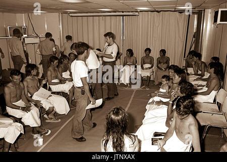 Vietnamesische Flüchtlinge werden untersucht und an Bord der USS BLUE RIDGE (LCC 19) verarbeitet. Die 35 refugeees - Stockfoto