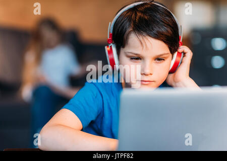 Portrait von konzentrierten kleinen Jungen in Kopfhörer mit Laptop - Stockfoto
