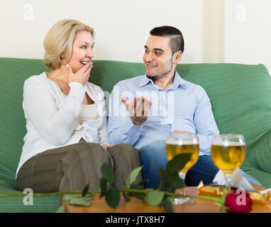 Lächelnd erwachsener Sohn gratulieren ältere Mutter und schlägt einen Toast - Stockfoto