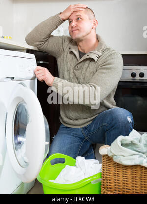 Mann hält seinen Kopf in der Nähe der Waschmaschine denken an, wie sie zu verwenden. Kerl, Wäscheservice - Stockfoto