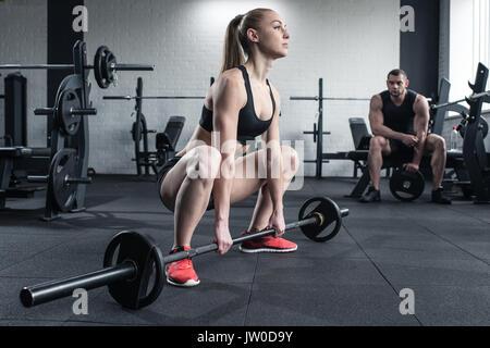 Frau tun Krafttraining mit Langhantel während man im Fitnessstudio sitzen - Stockfoto