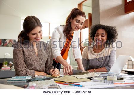 Weibliche Innenarchitekten surfen Fabric swatches am Schreibtisch - Stockfoto