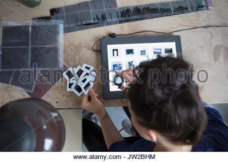 Ansicht von oben Fotografin Überprüfung fotografische Folien mit Linse Lupe Lupe in art studio - Stockfoto