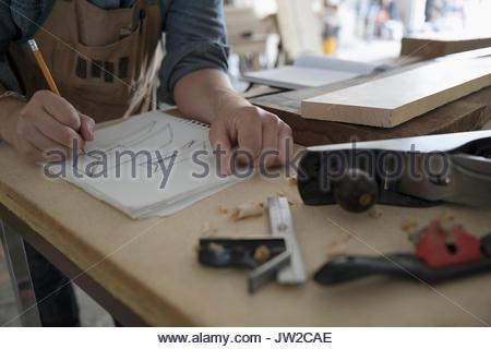 Close up männliche Tischler Skizzieren in Notebook an der Werkbank - Stockfoto