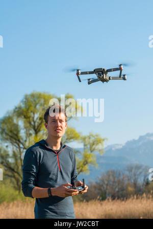 Junger Mann controlling fliegenden Quadrocopter, ferngesteuerte Drohne mit Kamera, DJI Mavic - Stockfoto