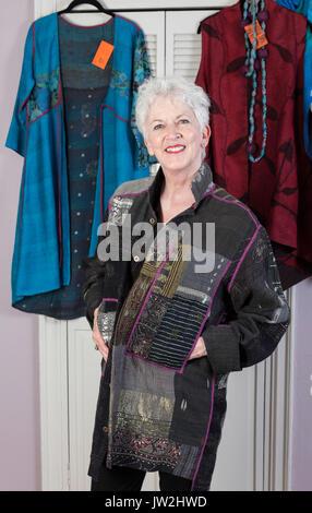 Attraktive ältere Frau, die versucht, auf Designer Kleidung, NYC, USA - Stockfoto