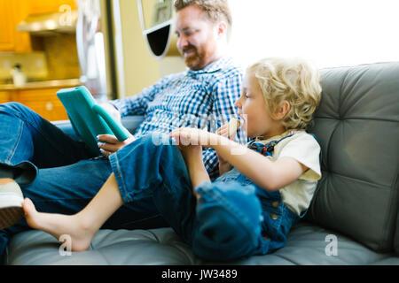 Junge (4-5) und man mit digitalen Tablet auf dem Sofa im Wohnzimmer. - Stockfoto